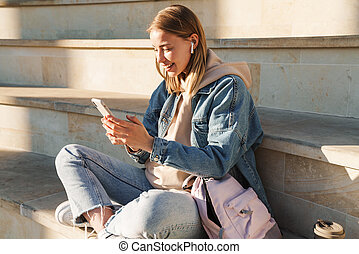 Cheerful young blonde girl using mobile phone while sitting on steps otdoors