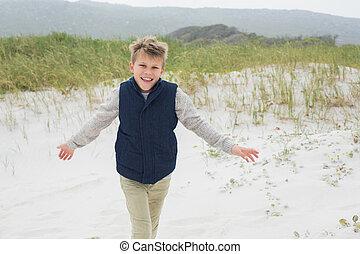 Cheerful young boy running at beach