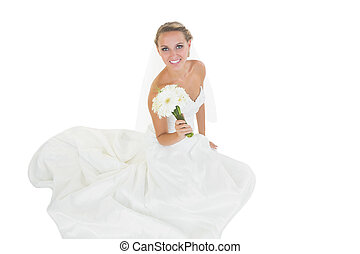 Cheerful young bride sitting on floor showing her bouquet