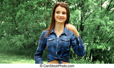 cheerful young brunette is standing on the street in a shirt...