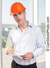 Cheerful young builder is creating the plan of new project