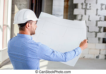 Cheerful young builder is studying the layout of new project