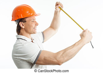 Cheerful young builder is working with tape-line