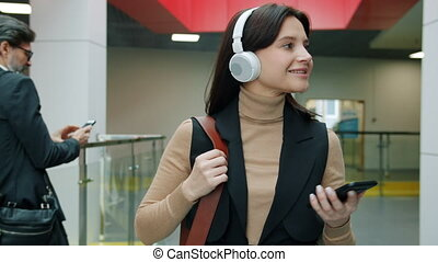 Cheerful young business lady walking in lobby wearing ...