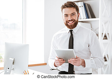 Cheerful young businessman holding tablet computer in hands....