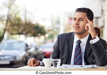 Cheerful young businessman is relaxing in cafeteria