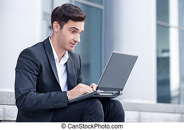 Cheerful young businessman is working with notebook