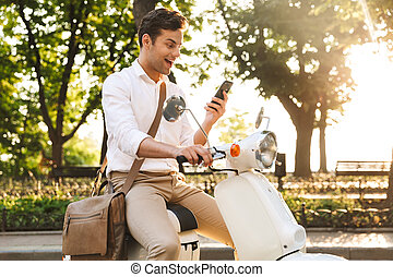 Cheerful young businessman sitting on a motorbike