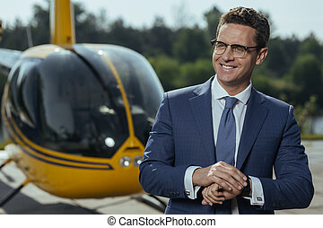 Cheerful young businessman smiling before helicopter ride