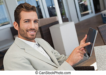 Cheerful young businessman working with digital tablet