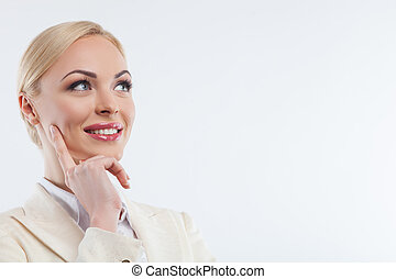 Cheerful young businesswoman is dreaming about future