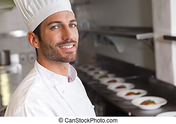 Cheerful young chef smiling at camera