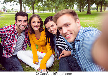 Cheerful young college students in park