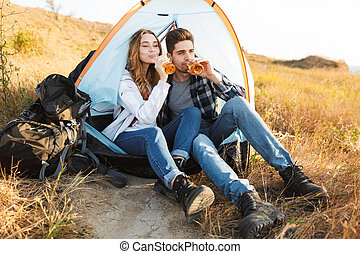 Cheerful young couple camping, sitting
