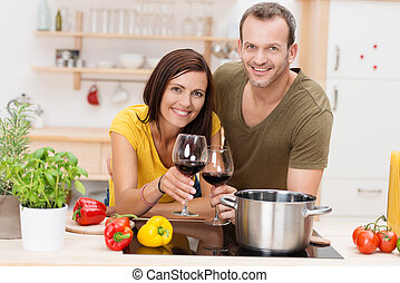 Cheerful young couple cooking a meal