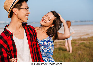 Cheerful young couple hugging outdoors