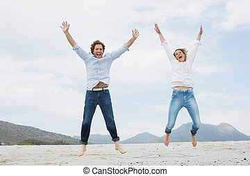Cheerful young couple jumping at be