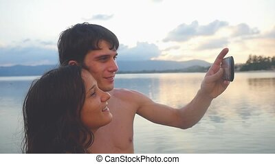 Cheerful young couple on the beach take a selfie portrait at sunset. Slow motion. People enjoying vacations concept.