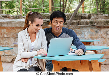 Cheerful young couple sitting and using laptop