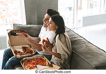 Cheerful young couple sitting on a couch at home