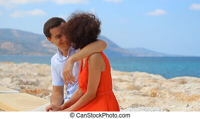 Cheerful young couple sitting on pier