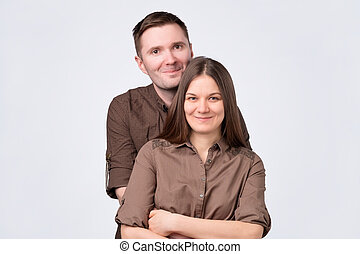 young couple standing on white background, hugging smiling at camera