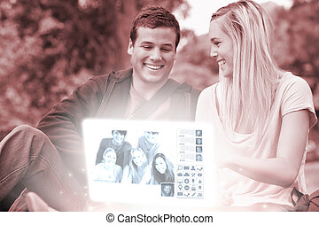 Cheerful young couple watching photos together on digital interface in bright park