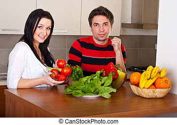 Cheerful young couple with vegetables in kitchen