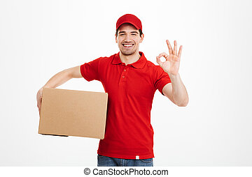 Cheerful young delivery man showing okay gesture.