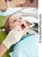 Cheerful young dentist is checking tooth of child