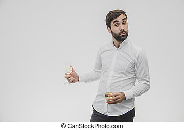 Cheerful young entrepreneur drinks champagne. During this celebrating Valentine's day. Dressed in white shirt.