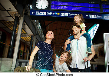 Cheerful young family at the train station. Dad, mom, son and daughter standing under an electronic scoreboard and smiling happily. Father keeps daughter on shoulders. Waggish boy looks into camera.