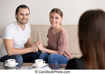 Cheerful young family couple on consultation. Holding hands and