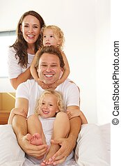 Cheerful young family in bed at home