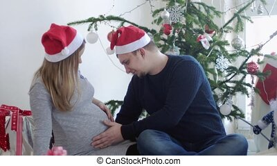 Cheerful young family in Santa cap. Husband touch belly his pregnant wife near beautiful decorated Christmas tree. slow motion. 3840x2160