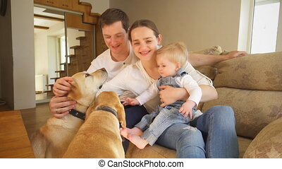 Cheerful young family with two dogs pets at home. Positive emotions