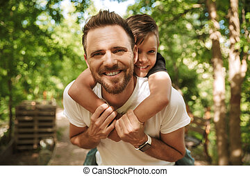 Cheerful young father have fun with his little son