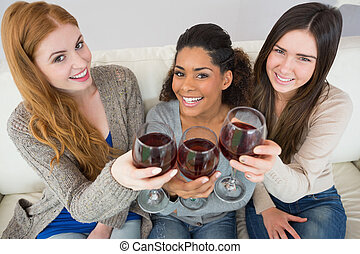 Cheerful young female friends toasting wine glasses - High ...