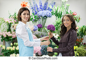 Cheerful young florist is serving her customer