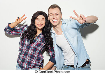 Cheerful young friendly couple is gesturing positively