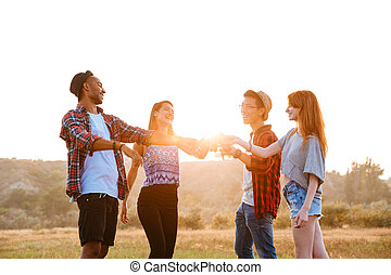 Cheerful young friends drinking beer and soda outdoors