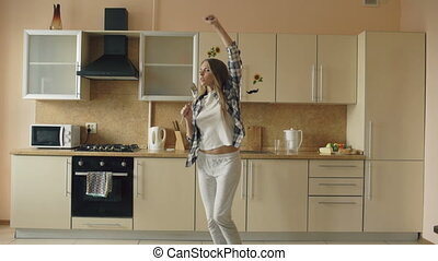 Cheerful young funny woman dancing and singing with ladle...