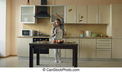 Cheerful young funny woman dancing and singing with ladle while while cooking in the kitchen at home