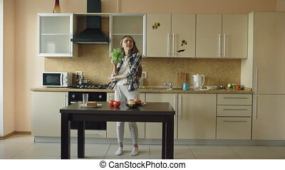 Cheerful young funny woman dancing and singing with lettuce microphone while cooking breakfast