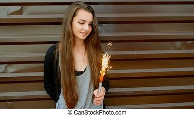Cheerful young girl having fun with sparkler in front of modern wall painted in brown color