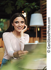 Cheerful young girl holding a tablet