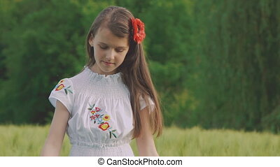 Cheerful young girl in embroidery dress posing at camera in the wheat field