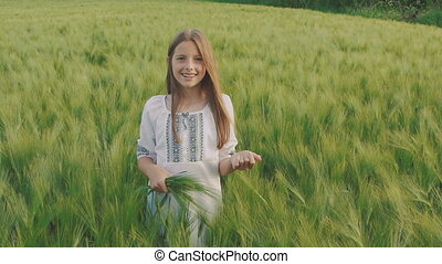 Cheerful young girl in embroidery dress posing with wheatears in a hand in field
