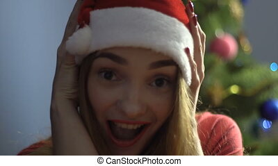 cheerful young girl in santa hat smiling on camera. christmas mood