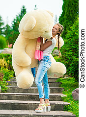 cheerful young girl posing with a big teddy bear in the park on the stairs
